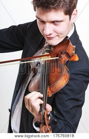 Music passion hobby concept. Creepy young man man dressed elegantly playing on wooden violin. Studio shot on white background