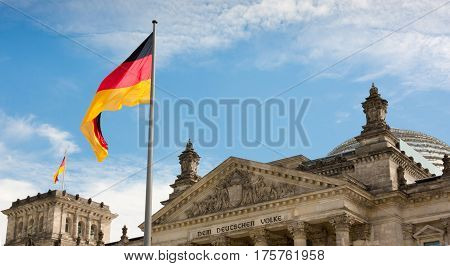 Waving German flag closeup over the Reichstag, Parliament building of Berlin. Germany