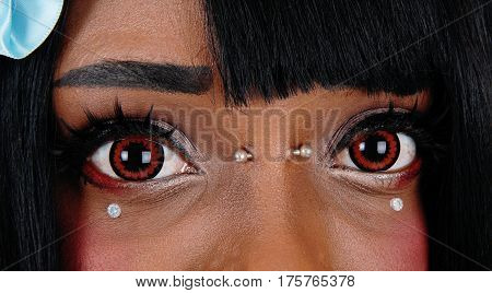 A closeup image of the beautiful big eyes of a African American woman with some body piercing and brown eyes.