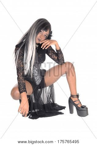 A gorgeous African American woman crouching in a black corset and gray black hair on the floor isolated for white background.