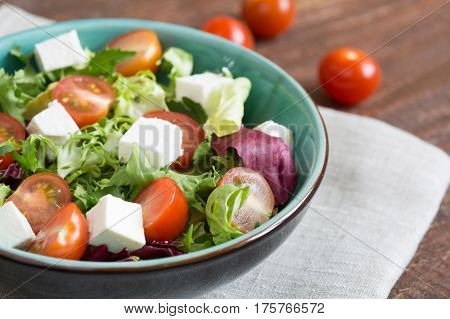 Salad with cherry tomatoes, Radicchio lettuce, frize, arugula and feta on wooden table