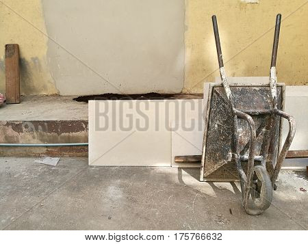 Construction metal wheelbarrow cart standing upside at the right corner on the construction site abandon building wall sand truck cart