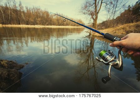 Hand with a fishing rod and reel on the summer lake