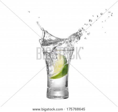 shot of vodka or tequila with lime slice and splash isolated on white background. Lime is falling in the alcohol drink. Splash of vodka  from the falling piece of lime