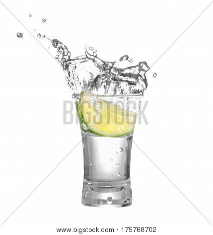 shot of vodka or tequila with lime slice and splash isolated on white background. Lime is falling in the alcohol drink. Splash of vodka  from the falling piece of lime. Clipping path