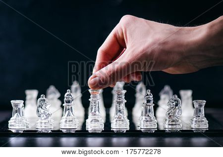 Hand of man keep a figure of chess. Chess business concept of victory. Chess figures in a reflection of chessboard. Game. Competition and intelligence concept.