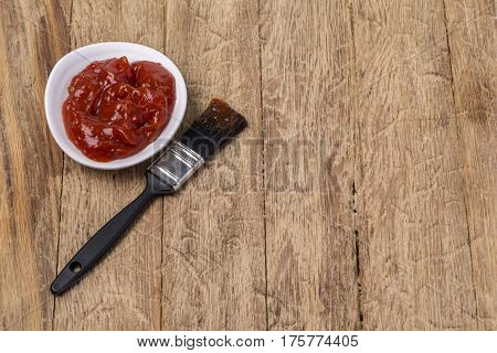 Barbecue sauce with basting brush over wooden table with room for copy space.