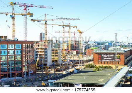 Helsinki Finland - August 5 2012: Construction of new modern residential micro-district in area West Harbour. High-rise cranes working in building of multi-storied buildings of glass & concrete
