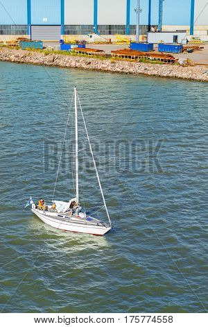 Helsinki Finland - August 5 2012: Sailing regatta in Bay of West Harbour. Sailing ship yacht involved in water sports. Young family with children raise the sail on sailboat. Scandinavia Suomi