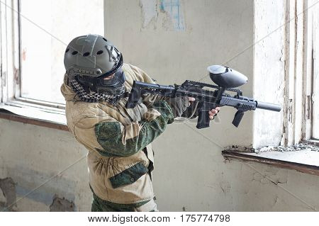 Shot of militaty man aiming in mask with paintball weapon