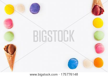 Multicolored Cake Macarons Or Macaroon And Waffle Cones In The Form Of Frame On The White Background