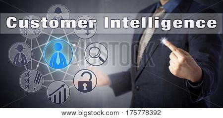 Businessman in blue suit is accessing Customer Intelligence. Information technology management metaphor and business concept combining customer relationship management and business intelligence.