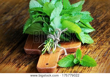 Fresh mint leaves herb on rustic wooden table ready for drying