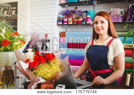 attractive young girl working in a flower shop, Woman floristry works with laptop, takes orders on the Internet