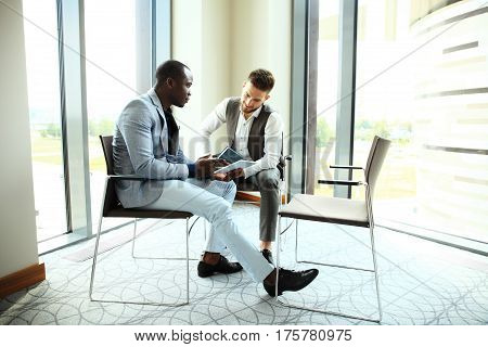 Image of two young businessmen using touchpad at meeting