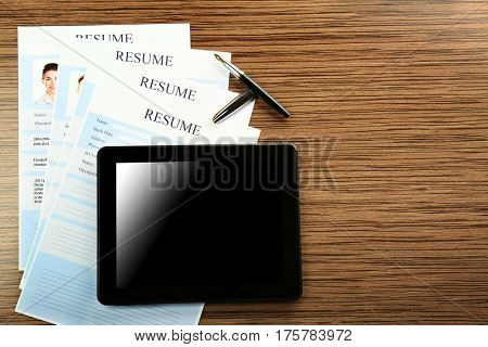 Employer workplace with tablet and resumes