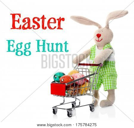 Easter hunt concept. Toy bunny with colorful eggs in mini shopping cart on white background