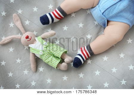 Cute little baby with bunny toy lying in cradle at home