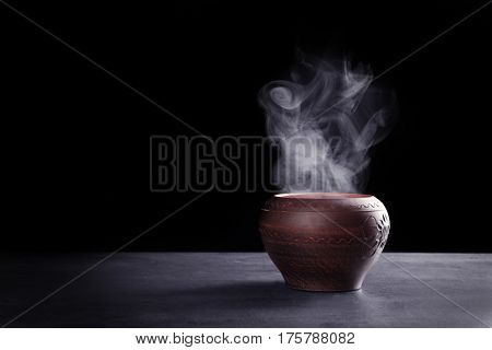 Ceramic pot with hot liquid on table against dark background