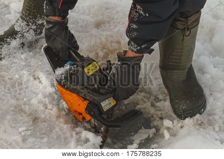 Man cutting chainsaw shell in ice winter fishing weather savior