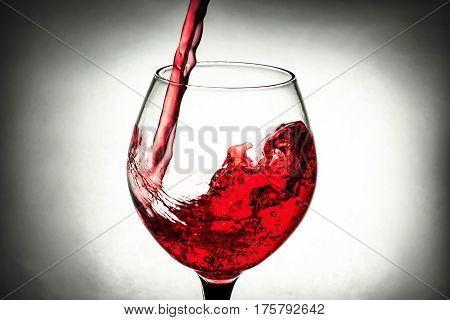 red wine in a glass splash in grey background