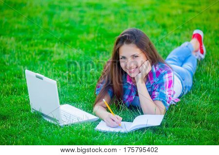 beautiful young girl lying on the field with laptop and copybook on the wonderful grass background