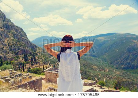 beautiful young woman standing in front of splendid mountain and ruins background in Greece