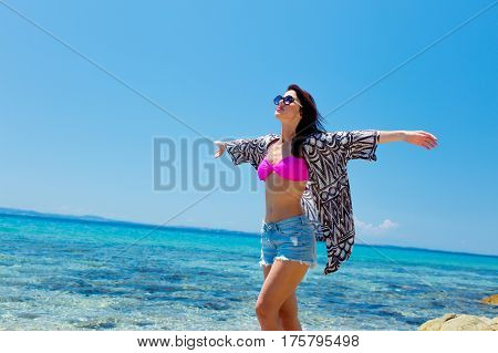 photo of beautiful young woman standing on the coast and relaxing in Greece