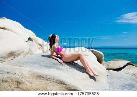 beautiful young woman lying on the wonderful stone coast in greece in swimsuit