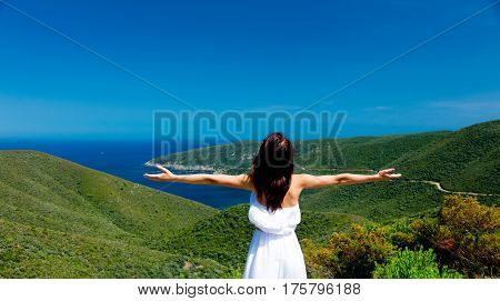 beautiful young woman standing on the wonderful mountains and sea background in greece