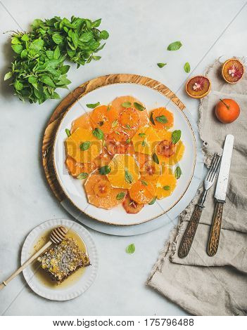 Fresh mixed citrus fruit salad with mint and honey on white ceramic plate over grey background, top view. Vegan, vegetarian, healthy, dieting, detox food, clean eating concept