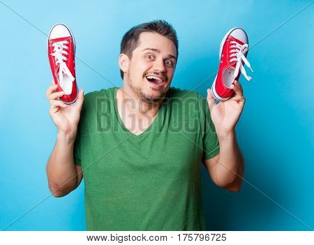handsome young man holding red gumshoes on the wonderful blue background