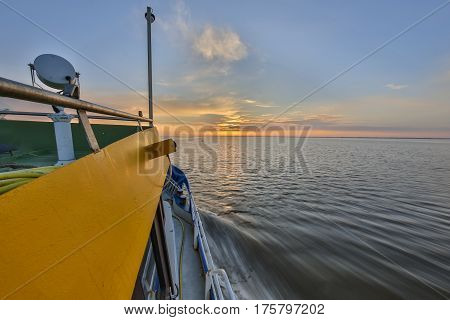 Ultra wide angle shot of travelling passenger ship in the early morning under rising sun
