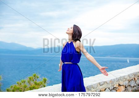 photo of beautiful young woman standing on the road on the sea background in Greece