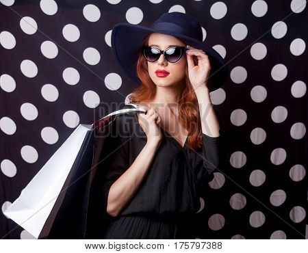 beautiful surprised young woman with shopping bags standing in front of the wonderful dotted background