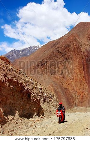 Nepal Himalayas the kingdom of Upper Mustang - April 2015: A motorcyclist on a motorcycle rides a mountain road in the mountains of the Himalayas. Nepal. Kingdom