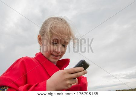 Girl With Cell Phone And Cloudy Sky