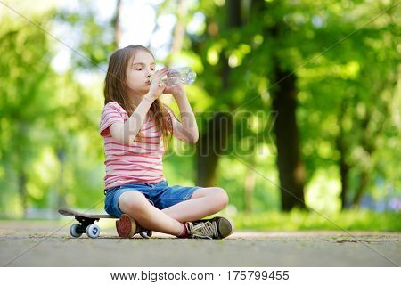 Pretty Little Girl Drinking Water While Sitting On A Skateboard Outdoors On Beautiful Summer Day