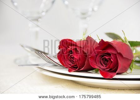 red roses on plate with silverware for romantic dinner
