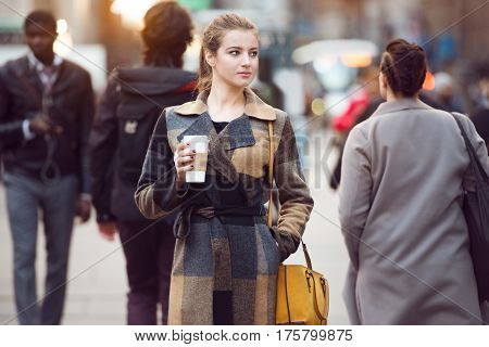 Young adult businesswoman walking on city street to the work in the group of multicultural people. Woman holding coffee cup and looking to the side.