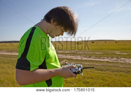 Remote control for quadrocopter, close-up. Transmitter for controlling moving device in male hands, blurred nature background. Electronics, hobby, aeromodelling concept