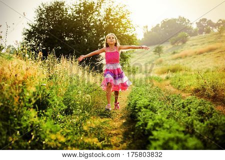 Happy little girl running on the grass. Running open arms little happy girl green meadow field track