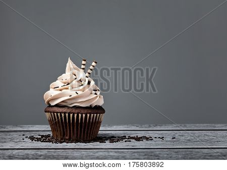Chocolate cupcake with buttercream icing over a grey background