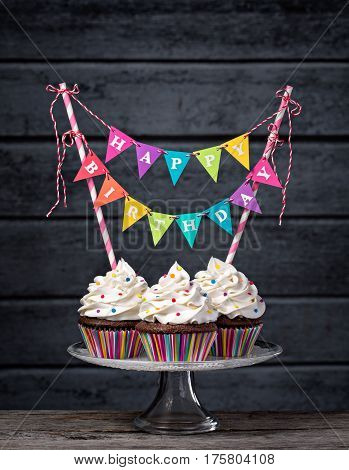 Three chocolate cupcakes with vanilla buttercream icing sprinkles and a colorful Happy Birthday banner.