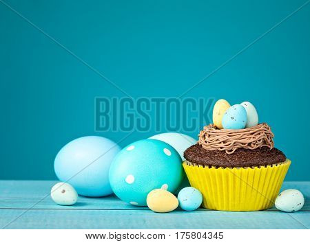 Easter Eggs and cupcake with Candy on a blue background.