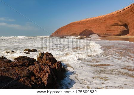 Red arches and rocky beach at the Atlantic Ocean in the region Sous-Massa-Draa, Sidi Ifni, Legzira, Morocco, Africa.