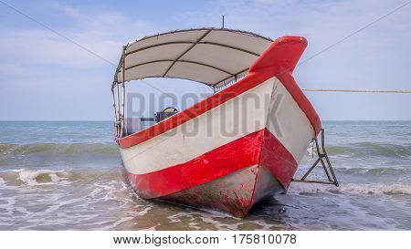 Longtail boat with red and white stripes waiting for passengers on beautiful monkey beach in Penang national park, Malaysia