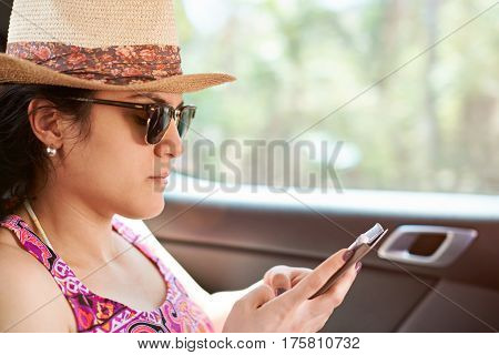 Casual Woman In Car Using Smartphone