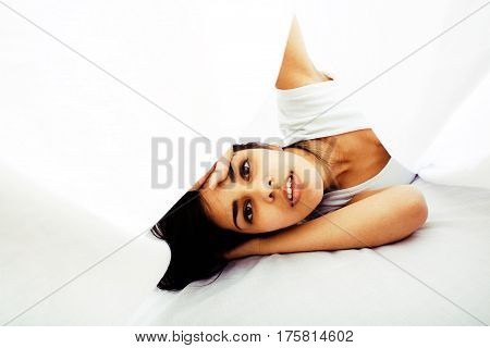 young pretty tann woman in bed among white sheets having fun, trying to sleep, fooling around, lifestyle concept at home. Cant sleep
