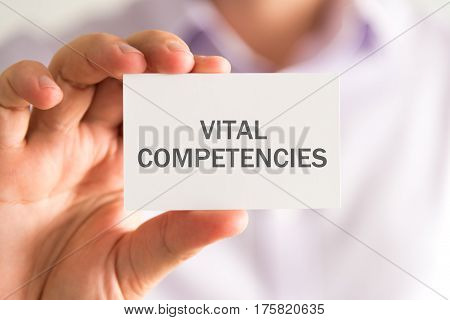 Businessman Holding A Card With Vital Competencies Message